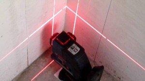 На фото - установка маяков на внутренний угол по лазеру, youtube.com