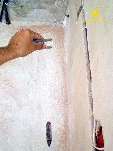 На фото - определения наиболее выступающего участка стены с помощью уровня