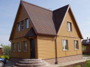 На фото - дом с сайдингом блок-хаус из пластмассы, roofmaster.ru