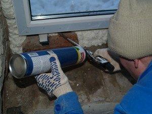 На фото - заделывание щелей окна монтажной пеной, domarem.ru