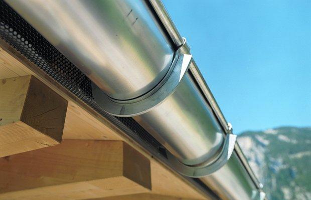Фиксирование металлического водостока на деревянной поверхности