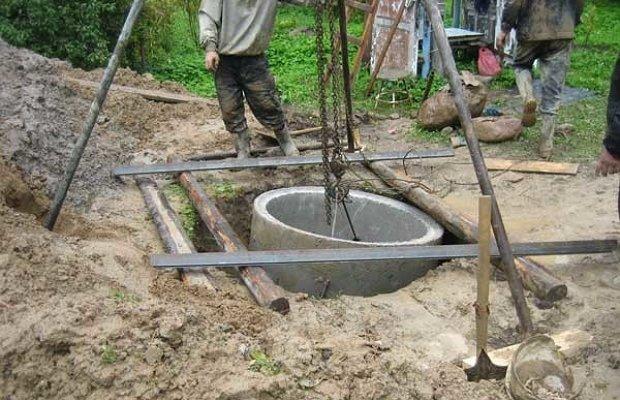 Опускание кольца из бетона в подготовленную яму