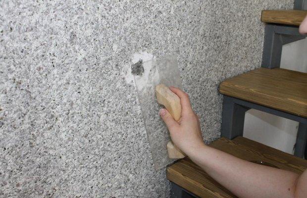 Используем шпатель для удаленияобоев со стены