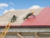 Рабочие укладывают черепицу на крыше