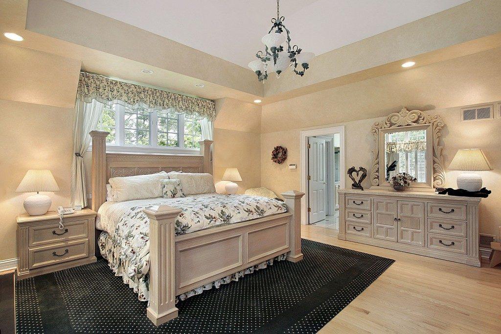 Спальня бежевого цвета смассивной мебелью более тёмного оттенка