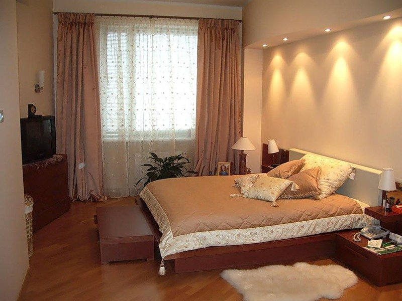 Коричневая мебель разбавляет монохромность бежевой спальни