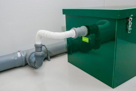 Процесс подсоединения жироуловителя к канализационным трубам