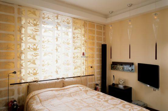 Спальня с кроватью под окном