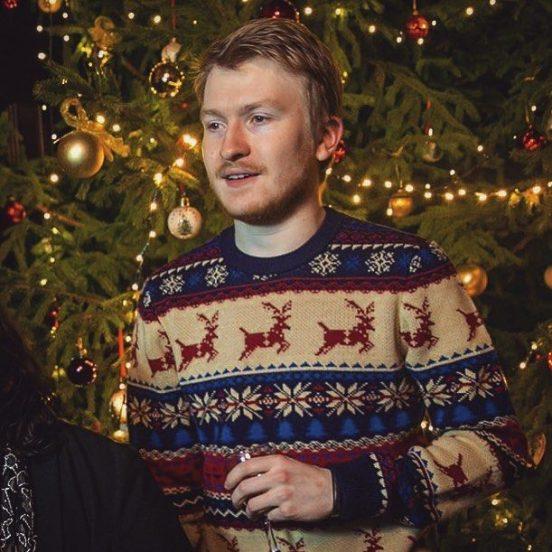 Данила Поперечный в новогоднем свитере на фоне елки