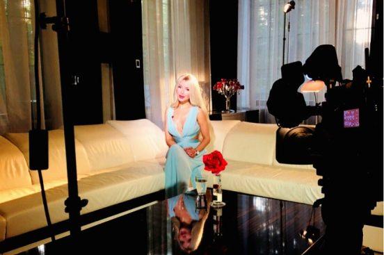 Алёна Кравец сидит на диване перед камерой