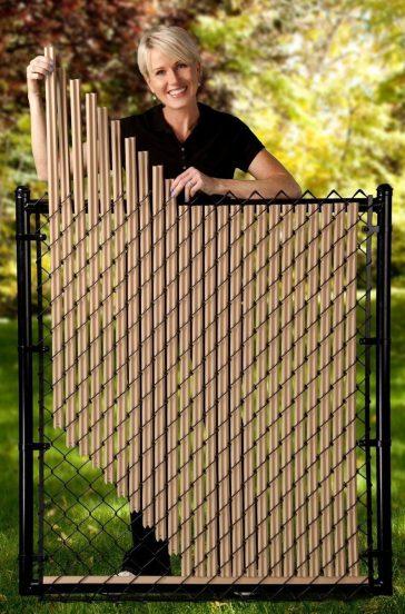Женщина оформляет забор из сетки рабицы дополнительными элементами