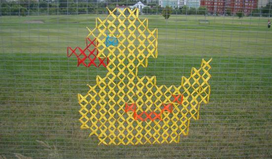 Утёнок из цветных лент на заборе из сетки рабицы