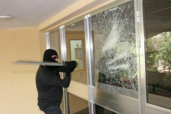 Бандит пытается разбить окно