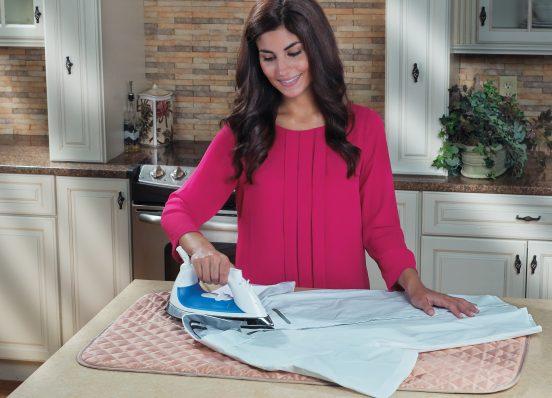 Девушка гладит рубашку на столе
