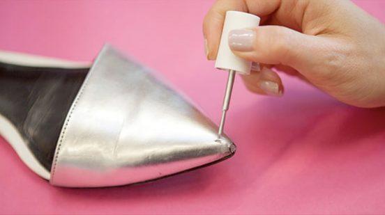 Девушка закрашивает потёртость на туфле лаком для ногтей