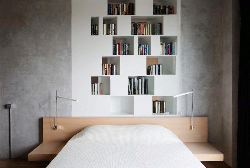 Белые полки в выемке в стене над кроватью